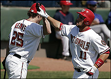 Ryan Zimmerman, right, is congratulated by Austin Kearns after hitting a home run in the Nationals' 9-6 exhibition victory. Zimmerman and the Mets' David Wright, both third basemen, grew up in the Tidewater area. (By Julie Jacobson -- Associated Press)